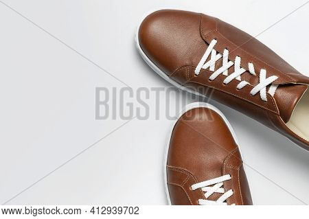 Leather Brown Men's Sneakers With White Laces And Rubber Soles On Gray Background. Flat Lay Top View