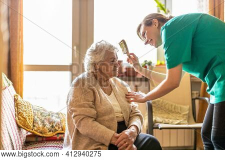 Female nurse taking care of a senior woman at home