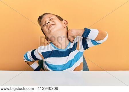 Adorable caucasian kid wearing casual clothes sitting on the table suffering of neck ache injury, touching neck with hand, muscular pain