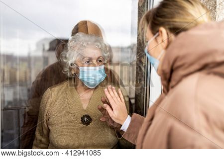 Woman visiting her grandmother in isolation during a coronavirus pandemic