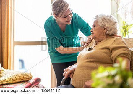 Friendly nurse supporting an elderly lady