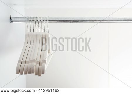 Empty Clothes Hangers, Closeup. Modern New White Closet. Many Wooden White Hangers On A Rod. Store,