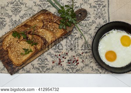Fried Eggs In A Rustic Iron Pan, Toast On A Wooden Board And A Cup Of Coffee For Breakfast. Top View