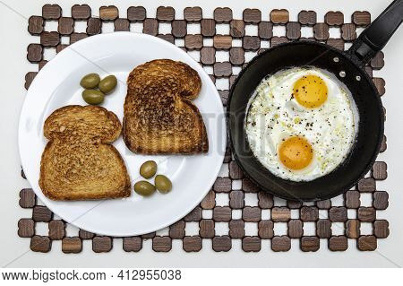 Fried Eggs In A Rustic Iron Pan, Toast On A Dish For Breakfast. Top View.