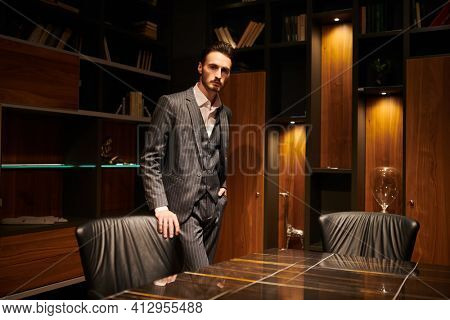 Handsome brunet man in an elegant suit man stands in a luxury office. Mafia. Male beauty, fashion.