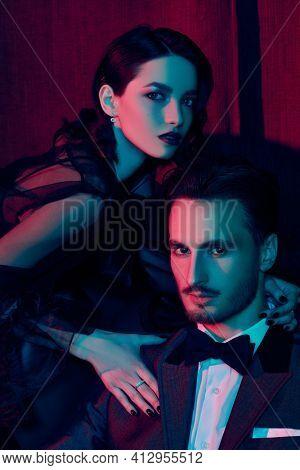 Beautiful elegant couple in fashionable evening clothes posing in a luxury apartment. Glamorous lifestyle. Fashion shot.