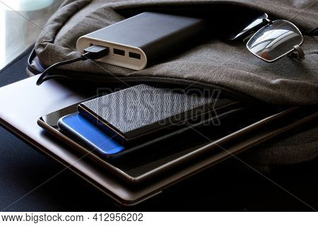 A Backpack Or Bag With Lots Of Gadgets And An External Battery - Power Bank Lies On A Black Surface.