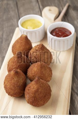 Typical Brazilian Snack Coxinha On A Wooden Board With Ketchup And Mustard.