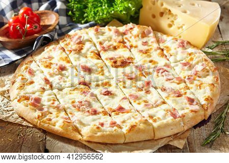Cheese and Bacon Pizza - homemade pizza dough topped with bacon, cheese and herbs. Italian pizza on baking paper with tomato and cheese on wooden table. Fast food pizza dinner rustic style