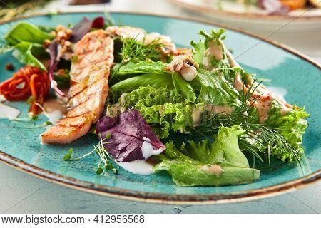 Seafood salad  with crispy buckwheat and mixed greens. Frutti di Mare salad with mixed seafood - salmon, calamari, octopus. Gourmet restaurant salad on blue plate