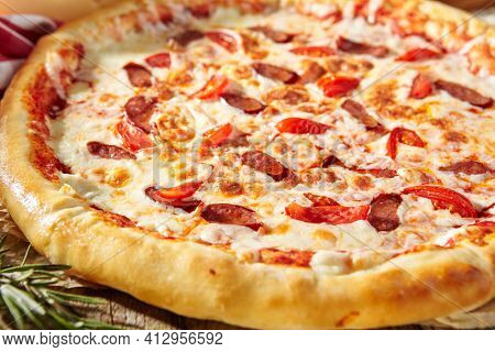 Spicy Sausage Italian Pizza with tomato, mozzarella cheese, sausage slice. Homemade pizza on baking paper with food ingredients on wooden table. Fast food or junk food pizza dinner rustic style
