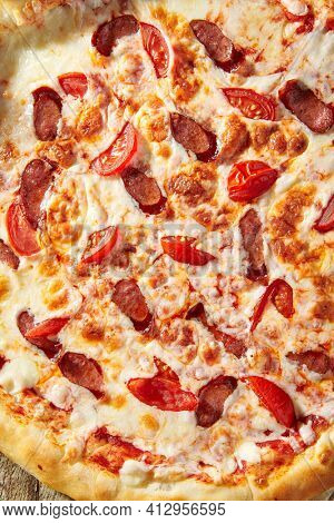 Spicy Sausage Italian Pizza with tomato, mozzarella cheese, sausage slice. Homemade pizza on baking paper with food ingredients on wooden table. Fast food or junk food pizza dinner top view