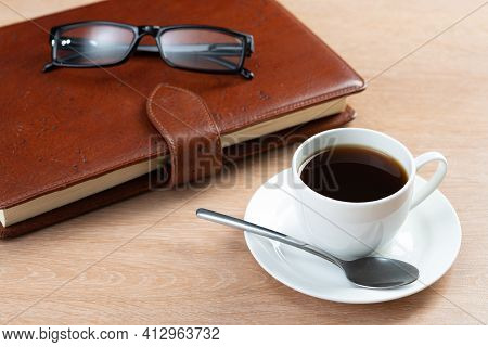 Brown Leather Notebook And Glasses On Wooden Table. Businessman Workspace With Cup Of Black Coffee.