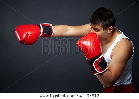 Portrait of young man in red boxing gloves fighting in isolation