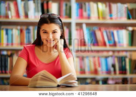 Portrait of cute girl with open book looking at camera in college library