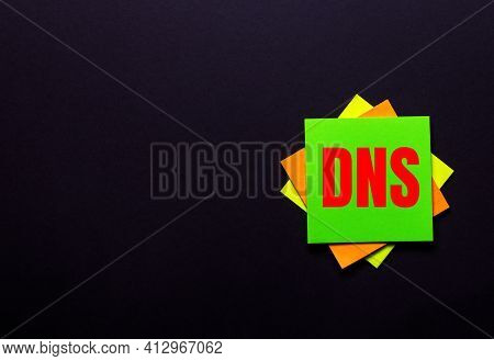 The Words Dns Domain Name System On A Bright Sticker On A Dark Background. Copy Space