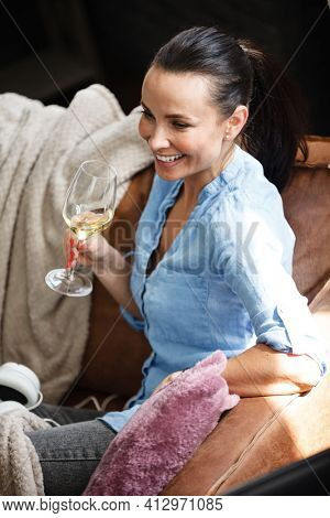 Leisure time concept. Happy beautiful woman drinks white wine from glass sitting on a couch indoors. Female spending her free day and relaxing at home alone.