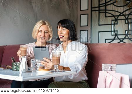 Two Mature Women Chatting And Using The Tablet Device While Having Lunch In Cafe