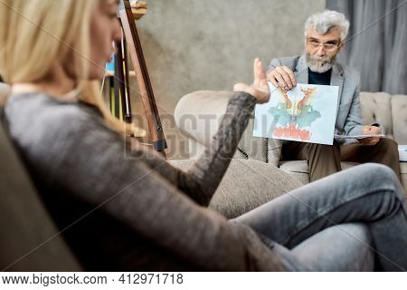 Psychotherapist Showing Rorschach Test Pictures To Young Caucasian Woman During Session In Office, S