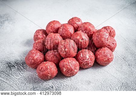 Raw Beef And Pork Meatballs With On Kitchen Table. White Background. Top View