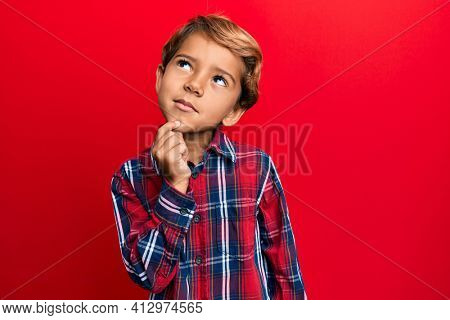 Adorable latin kid wearing casual clothes thinking concentrated about doubt with finger on chin and looking up wondering