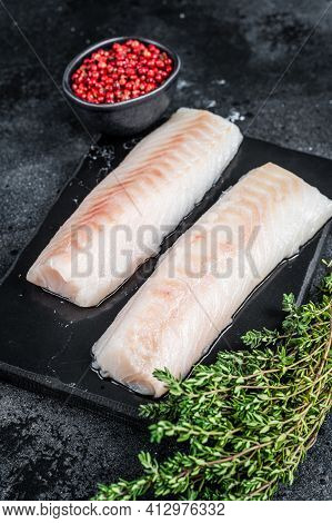 Raw Cod Loin Fillet Fish On Marble Board. Black Background. Top View