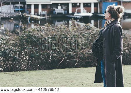 Side View Of Very Pregnant Blone Woman Taking A Walk By River Or Lake