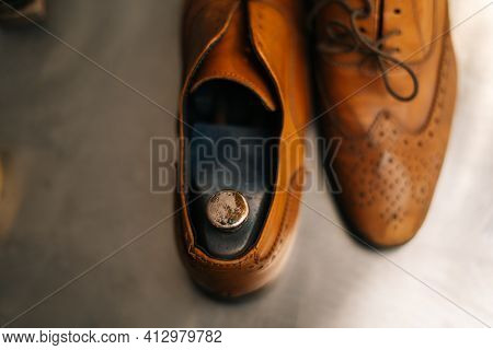Close-up View Of Old Light Brown Leather Shoes With Wooden Shoe Pad To Be Repaired In Dark Craft Sho
