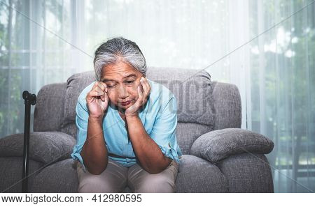 Portrait Images Of Asian Elderly Woman  Sitting Absent Lonely On The Sofa, Sad And Worried About Her