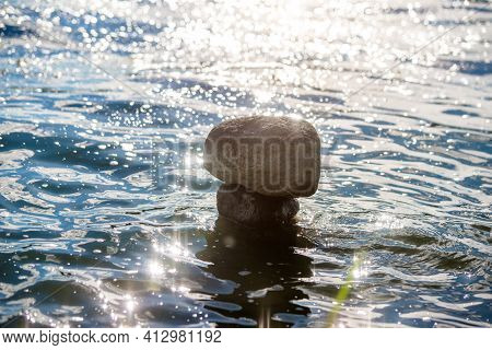A Stone Sculpture Stands In Seawater .a Stone Sculpture.