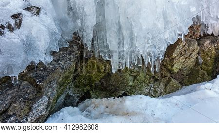 Early Spring. The Icicles On The Rocks Begin To Melt. There Is Loose Melted Snow On The Ground. Clos