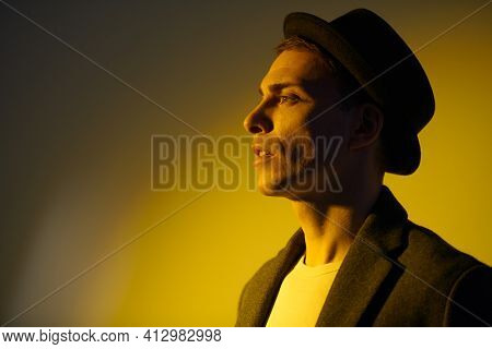 Portrait of a handsome middle-aged man in an elegant coat and a hat posing at studio in yellow light. Men's beauty, fashion. Lifestyle. Hipster man.
