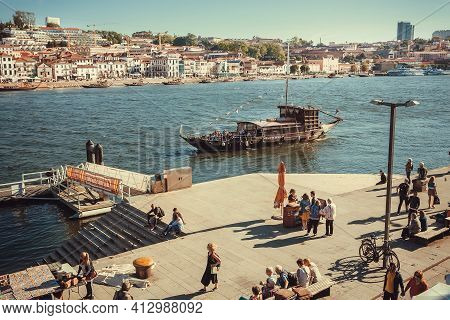 Porto, Portugal: Walking People In Historical Riverside Of Douro River, Cityscape At Sunny Day On 19