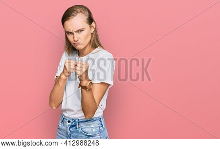 Beautiful young blonde woman wearing casual white t shirt ready to fight with fist defense gesture, angry and upset face, afraid of problem
