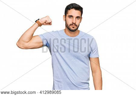 Young hispanic man wearing casual clothes strong person showing arm muscle, confident and proud of power