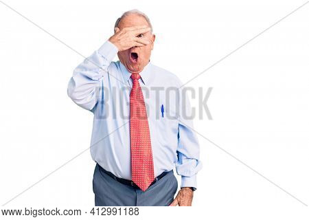 Senior handsome grey-haired man wearing elegant tie and shirt peeking in shock covering face and eyes with hand, looking through fingers with embarrassed expression.