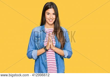 Young brunette woman wearing casual clothes praying with hands together asking for forgiveness smiling confident.