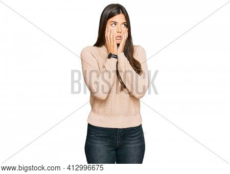 Young brunette woman wearing casual winter sweater tired hands covering face, depression and sadness, upset and irritated for problem