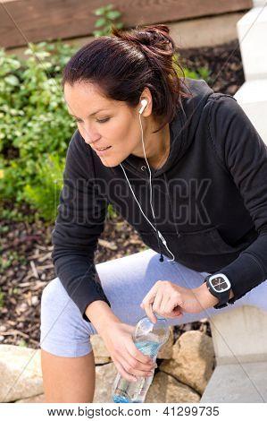 Tired woman relaxing after running sport bottle headphones sweatsuit