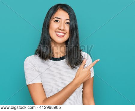 Beautiful asian young woman wearing casual white t shirt cheerful with a smile of face pointing with hand and finger up to the side with happy and natural expression on face