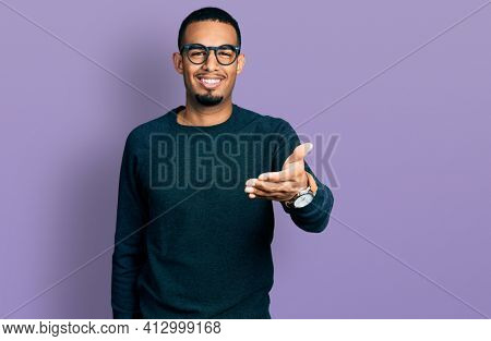 Young african american man wearing casual clothes and glasses smiling friendly offering handshake as greeting and welcoming. successful business.