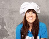 portrait of a female chef looking up, indoor poster