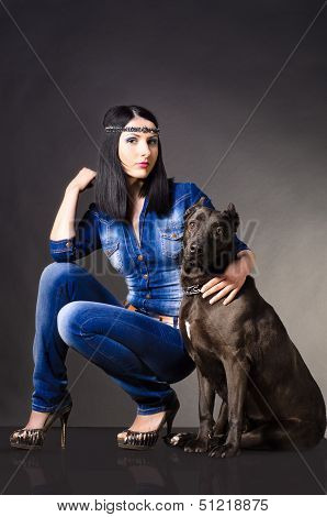 Beautiful young woman in jeans clothes sitting next to the dog poster