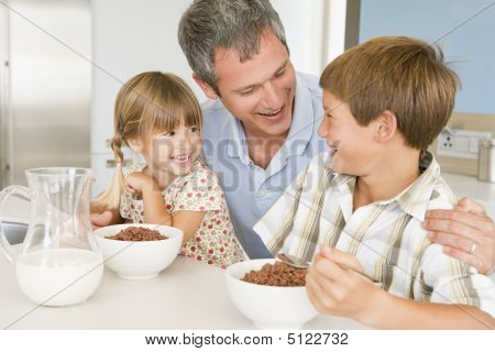 Father Sitting With Children As They Eat Breakfast