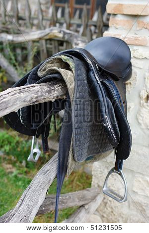 Old Saddle Hanging on Rustic Wood Pole Fence poster