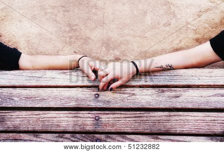 two people holding hands on a bench