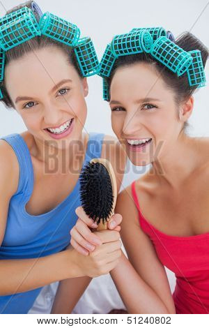 Happy girls in hair rollers holding hairbrush and singing at sleepover