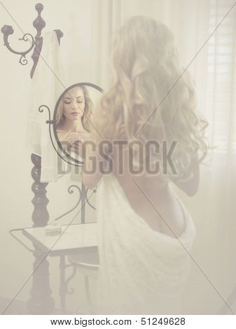 Nude elegant blonde woman in front of the mirror