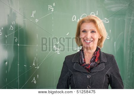 Cheerful professor standing in front of a chalkboard
