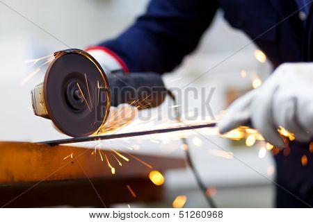 Worker grinding a metal bar